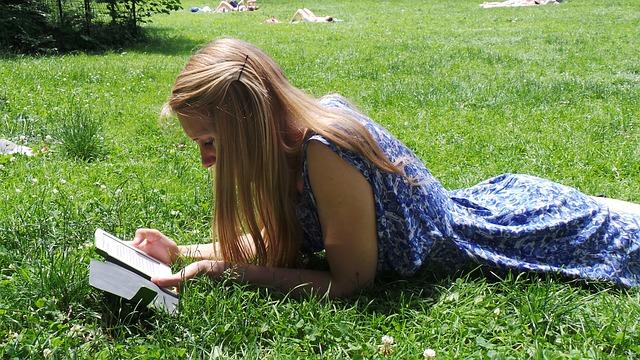電子書籍を草の上で読む少女