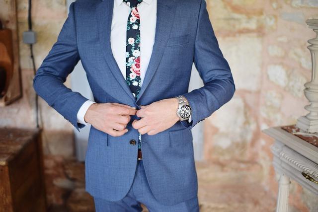 スーツのボタンをとめる男性
